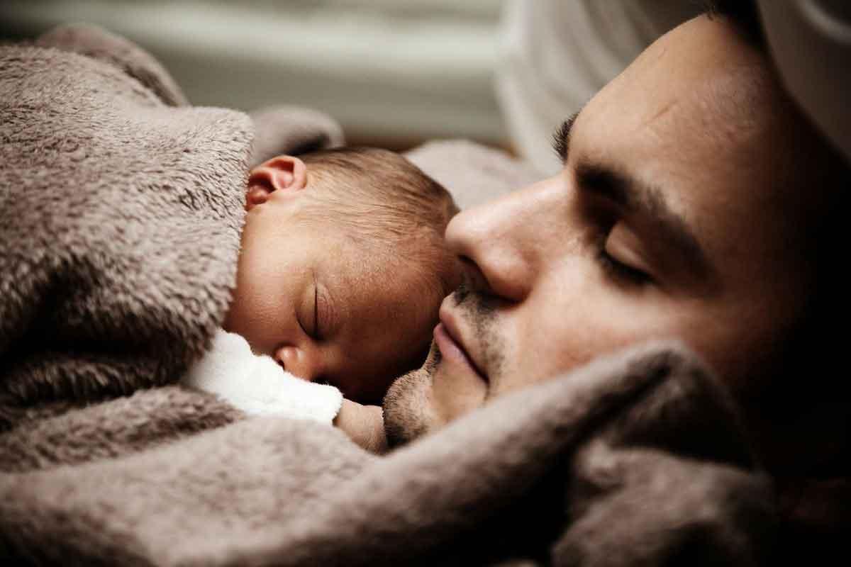 baby in bed met vader